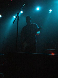 Bob Mould stares at the crowd before launching into The Act We Act